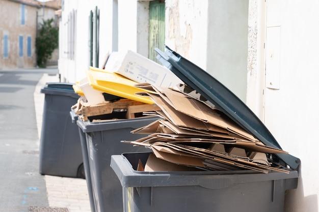 Pełny kosz na śmieci z tektury w mieście ulicy