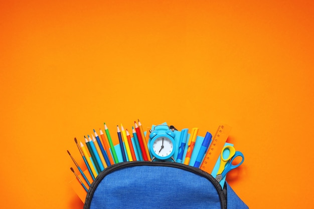 Pełny niebieski plecak szkolny z różnymi artykułami na pomarańczowym tle.