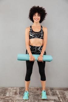 Pełny obraz beztroskiej sportowej kobiety trzymającej matę do ćwiczeń