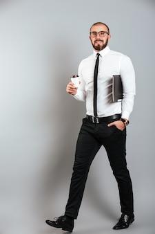 Pełny obraz młodego nieogolonego mężczyzny w okularach i garniturze chodzącego z kawą na wynos i laptopa w rękach, na białym tle nad szarą ścianą