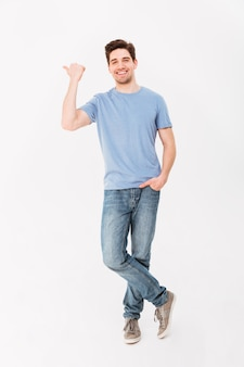 Pełny obraz przystojny mężczyzna raduje się i wskazuje palec na copyspace, odizolowywający nad biel ścianą