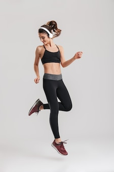 Pełny obraz silnej woli trenera fitness instruktora skoków odzieży sportowej ze słuchawkami bezprzewodowymi, na białym tle nad szarą ścianą