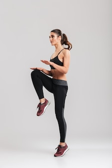 Pełny obraz silnej woli trenerki fitness instruktora rozgrzewki i ćwiczeń sportowych, izolowany na szarej ścianie