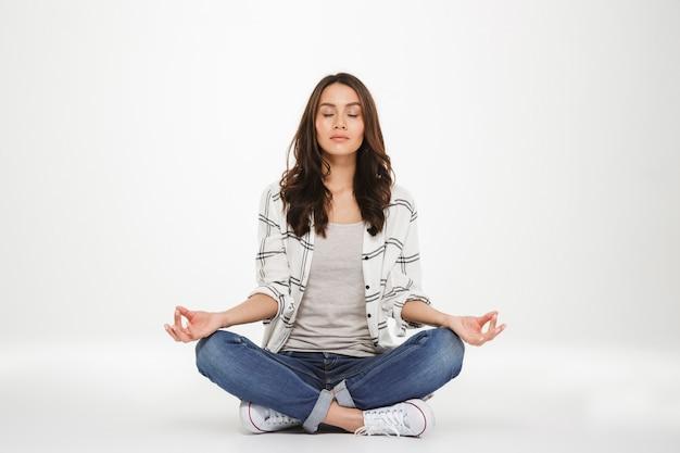 Pełny obraz skoncentrowanej kobiety w przypadkowych ubraniach, medytującej z zamkniętymi oczami, siedząc w pozycji lotosu na podłodze, na białym tle nad białą ścianą