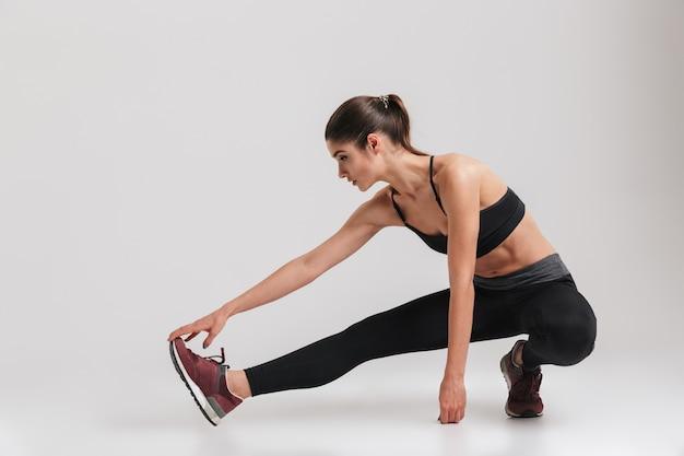 Pełny obraz sportowej kobiety z elastycznym ciałem kucającym i rozciągającym nogę, na białym tle nad szarą ścianą