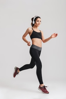 Pełny obraz sportowy kobiety w dresie bieganie i słuchanie muzyki przez słuchawki bezprzewodowe, na białym tle nad szarej ścianie