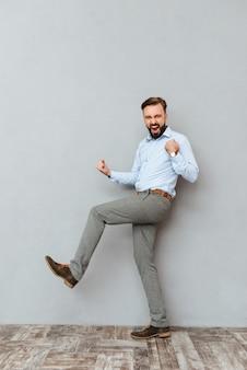 Pełny obraz szczęśliwy krzyczący brodaty mężczyzna w ubrania biznesowe