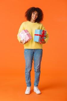 Pełny pionowy strzał atrakcyjna wesoła kobieta afroamerykanów przygotowana na święta, kupiona prezenty dla rodziny, uśmiechnięta wesoła trzymająca dwa zapakowane prezenty, stojący pomarańczowy
