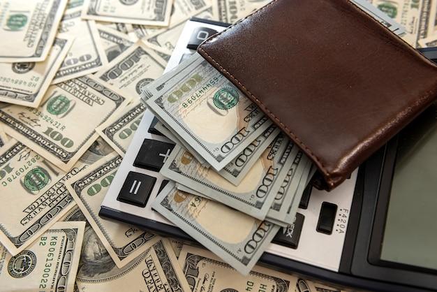 Pełny portfel banknotów 100 dolarów z kalkulatorem jako tło biznesowe, koncepcja oszczędności