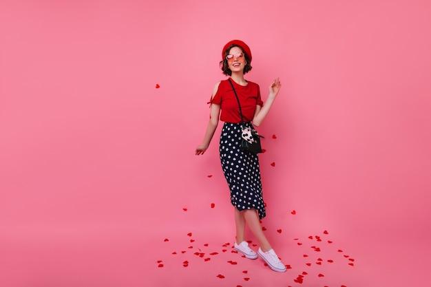 Pełny portret kaukaski kobieta w stylowej sukience stojącej pod konfetti. wspaniała francuska dziewczyna świętuje walentynki.