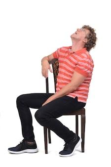 Pełny portret kręconego mężczyzny siedzącego bokiem na białym tle, patrzącego w górę