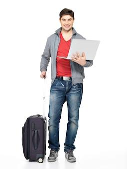 Pełny portret młodego uśmiechniętego szczęśliwego człowieka z walizką i laptopem na białym tle