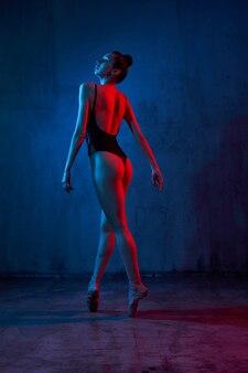 Pełny portret młodej baletnicy w czarnej bieliźnie i pointes tańczy