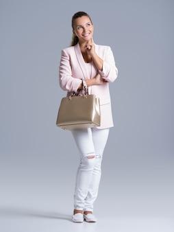 Pełny portret młodej kobiety szczęśliwy z torebką pozowanie w studio.