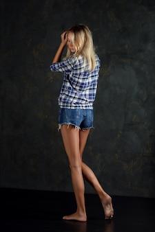 Pełny portret młodej seksownej kobiety w jeansowych szortach, niebieskiej koszuli w kratę, bosych stopach i bez makijażu.