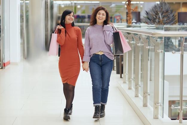 Pełny portret młodych kobiet pozujących w centrum handlowym z torbami na zakupy, kobiet w strojach codziennych