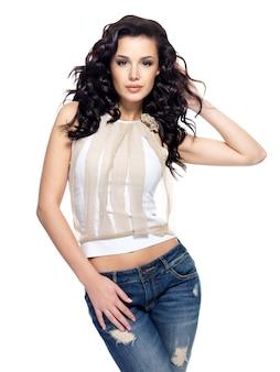 Pełny portret modelka z długimi włosami, ubrana w niebieskie dżinsy