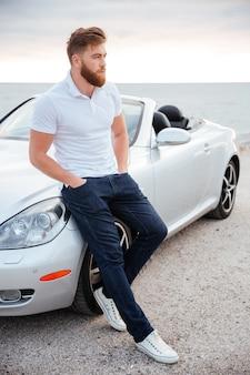Pełny portret pewnej siebie brodaty, opierającej się na swoim luksusowym samochodzie