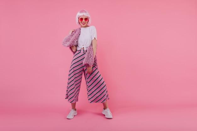 Pełny portret pewnej siebie młodej kobiety w modnych spodniach. kryty ujęcie inspirowanej kobiety w peruke i okularach przeciwsłonecznych na jasnoróżowej ścianie