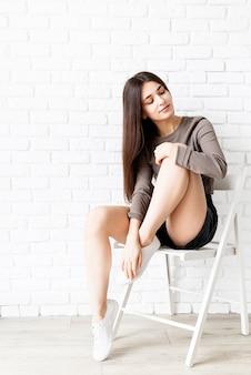 Pełny portret pięknej brunetki z długimi włosami, ubranej w brązową koszulę i czarne skórzane szorty, siedzącej na krześle z zamkniętymi oczami