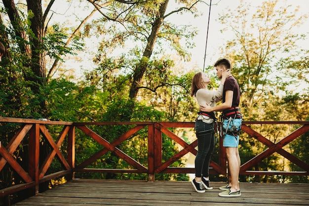 Pełny portret pięknej pary obejmującej się i bawiącej się zjeżdżalni linowej, podczas gdy dziewczyna trzyma twarz chłopaka ręką na platformie kolejki linowej przez drzewa.