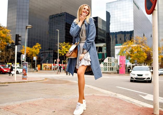 Pełny portret stylowej, całkiem wesołej blondynki pozującej na ulicy w pobliżu budynków centrum biznesowego, ubrana w płaszcz i trampki, modowy styl życia, pozytywny nastrój.