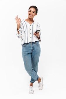 Pełny portret swobodnej uśmiechniętej młodej afrykańskiej kobiety stojącej na białym tle nad białą ścianą, słuchającej muzyki przez bezprzewodowe słuchawki, trzymającej telefon komórkowy, pokazujący ok
