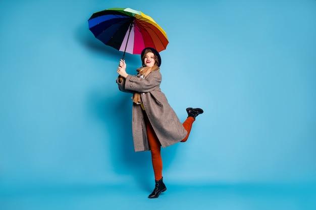 Pełny portret szalonej, funky podróżniczki, podnoszącej się, trzymaj kolorowy parasol nadmuch powietrza nosić długi szary płaszcz sweter pomarańczowe spodnie kapelusz buty.
