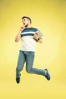 Pełny portret szczęśliwego człowieka skaczącego z gadżetami na żółto