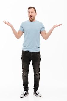 Pełny portret szczęśliwego mężczyzny z zarostem w swobodnym podnoszeniu ramion, wyrażający zdziwienie lub podniecenie