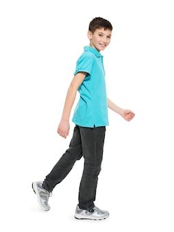 Pełny portret uśmiechniętego chodzącego chłopca nastolatka w dorywczo niebieski t-shirt na białym tle.