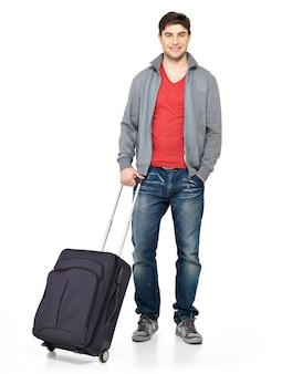Pełny portret uśmiechnięty szczęśliwy człowiek z szarą walizką na białym tle