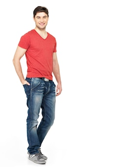 Pełny portret uśmiechnięty szczęśliwy przystojny mężczyzna w dorywczo czerwony t-shirt na białym tle na białej ścianie. piękny, młody chłopak pozowanie