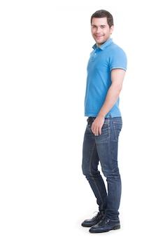 Pełny portret uśmiechnięty szczęśliwy przystojny mężczyzna w dżinsach stojący na białym tle na białej ścianie.