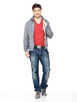 Pełny portret uśmiechnięty szczęśliwy przystojny mężczyzna w szarej kurtce, niebieskie dżinsy. piękny facet stojący na białym tle.