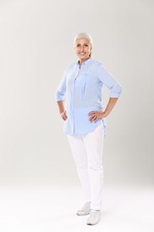 Pełny portret wesołej dojrzałej kobiety w niebieskiej koszuli i białych spodniach, stojącej z rękami na jej talii