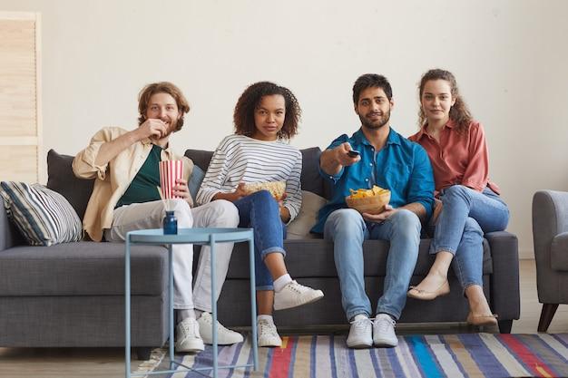 Pełny portret wieloetnicznej grupy przyjaciół, którzy razem oglądają telewizję, siedząc na wygodnej kanapie w domu i delektując się przekąskami