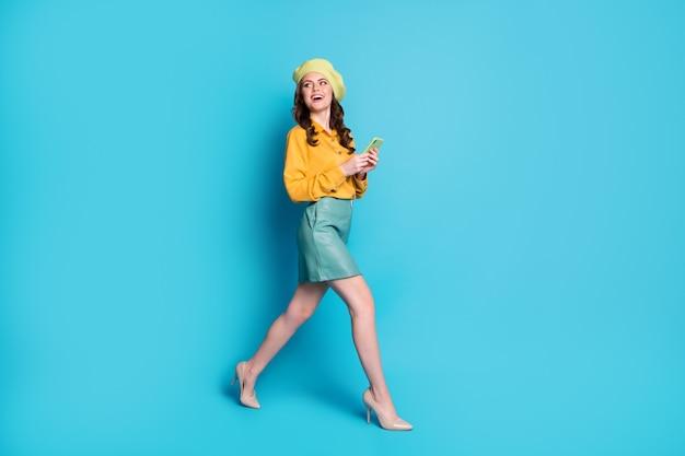 Pełny rozmiar zdjęcia pozytywnej wesołej dziewczyny iść spacer copyspace używać smartfona blogowania cieszyć się odpoczynkiem zrelaksować się nosić nakrycia głowy szpilki na białym tle nad niebieskim kolorem tła