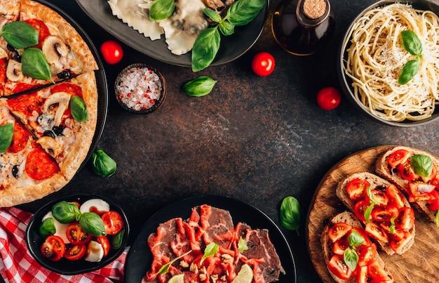 Pełny stół włoscy posiłki na talerzach na czarnym tle