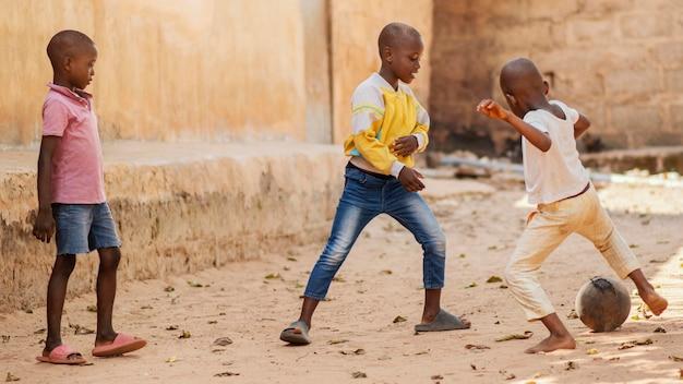 Pełny strzał afrykańskich dzieci grających w piłkę