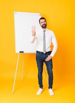 Pełny strzał biznesmen daje prezentaci na białej desce szczęśliwej i liczy trzy z palcami