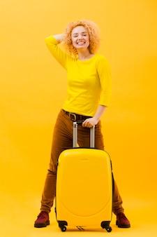 Pełny strzał blondynki kobieta z walizką