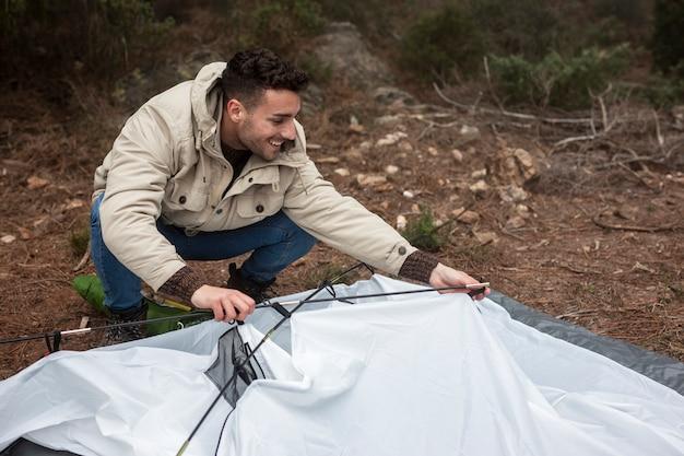 Pełny strzał buźkę człowieka rozbijając namiot