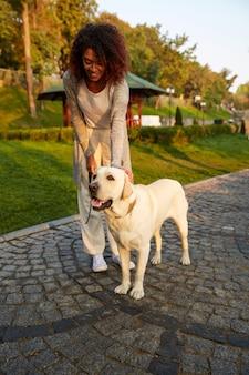 Pełny strzał całkiem zdrowa młoda dama spaceru rano w parku z psem