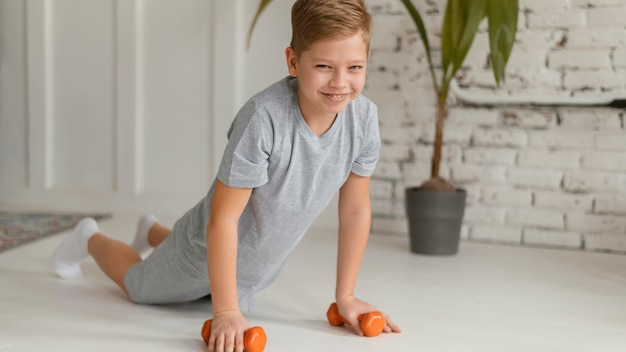 Pełny strzał chłopiec ćwiczeń w pomieszczeniu
