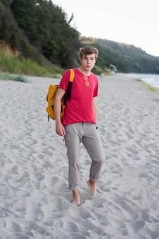 Pełny strzał chłopiec z plecakiem na plaży