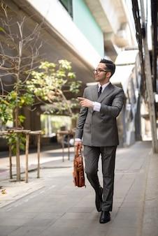 Pełny strzał ciała młodego przystojnego biznesmena perski wskazując palcem na ulicach miasta na zewnątrz