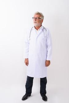 Pełny strzał ciała przystojny starszy brodaty mężczyzna lekarz stojący i myśli na białym tle