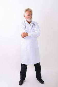 Pełny strzał ciała przystojny starszy brodaty mężczyzna lekarz stojący podczas myślenia i noszenia okularów ochronnych z rękami skrzyżowanymi na białym