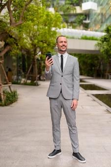 Pełny strzał ciała szczęśliwy biznesmen brodaty hiszpanie łysy myślenia i korzystania z telefonu z naturą w mieście